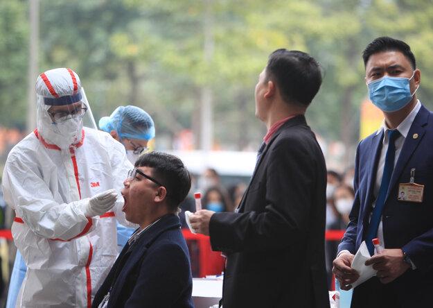 Zdravotníčka v ochrannom odeve odoberá vzorku bezpečnostnému pracovníkovi počas testovania na ochorenie COVID-19 v dejisku kongresu Vietnamskej komunistickej strany v Hanoji 29. januára 2021.