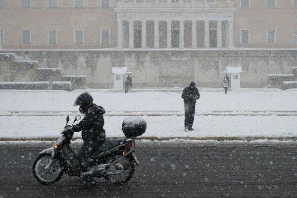 Zasnežené námestie pred budovou parlamentu v Aténach.