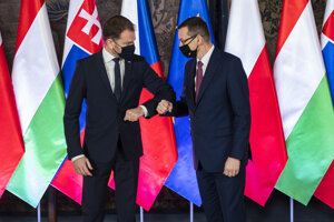 Poľský predseda vlády Mateusz Morawiecki (vpravo) a slovenský predseda vlády Igor Matovič sa zdravia počas spoločnej fotografie na kráľovskom hrade Wawel pred plenárnym zasadnutím predsedov vlád Vyšehradskej skupiny.