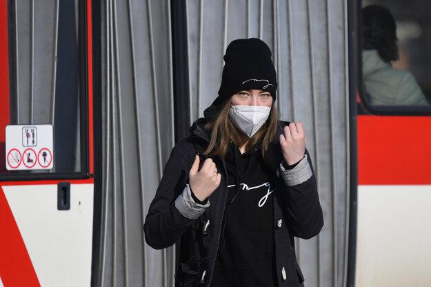 Cestujúca s respirátorom stojí na zastávke MHD v Prešove.