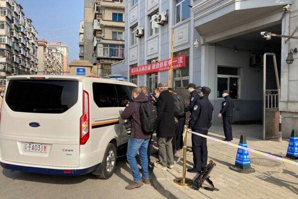 Novinári obklopujú policajné vozidlo po jeho príchode do budovy súdu v čínskom Tan-tungu 19. marca 2021.