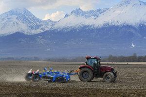 Na končiaroch sneh, dole na poli traktor v akcii.