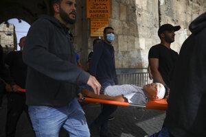 Palestínčania evakuujú zraneného protestujúceho počas násilných potýčkach medzi izraelskou políciou a Palestínčanmi v Jeruzaleme.