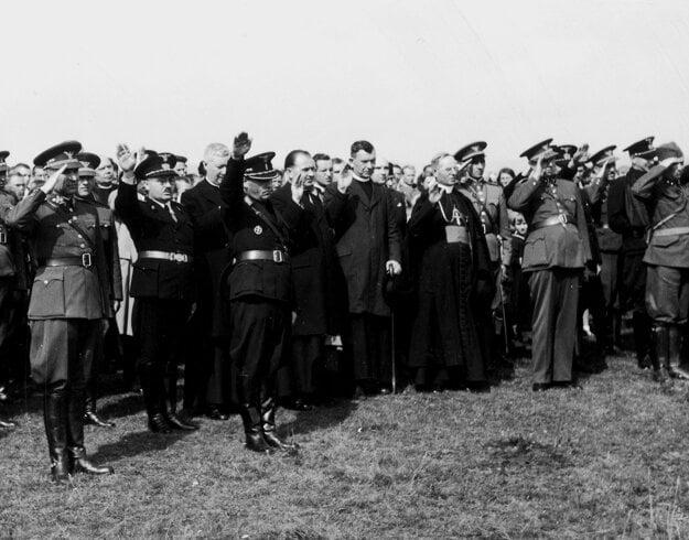 Ján Vojtaššák (v biskupskej reverende) hajluje spoločne s veliteľom Hlinkovej gardy Alexandrom Machom (v popredí s gardistickým dvojkrížom na uniforme) a vojakmi, ktorí prepadli s nacistami Poľsko.