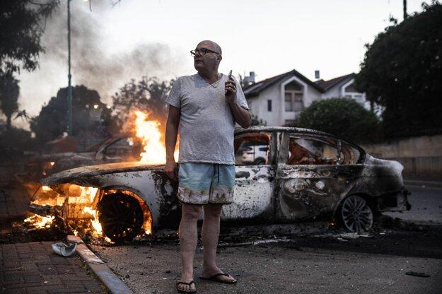 Muž stojí pri horiacom aute počas potýčok medzi arabskou komunitou a políciou v meste Lod.