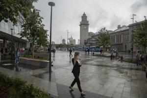 Žena s ochranným rúškom kráča ulicou v Moskve.