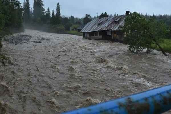 Rozvodnený potok Javorinka, ktorý berie so sebou starší dom v Podspádoch vo Vysokých Tatrách. Júl 2018.