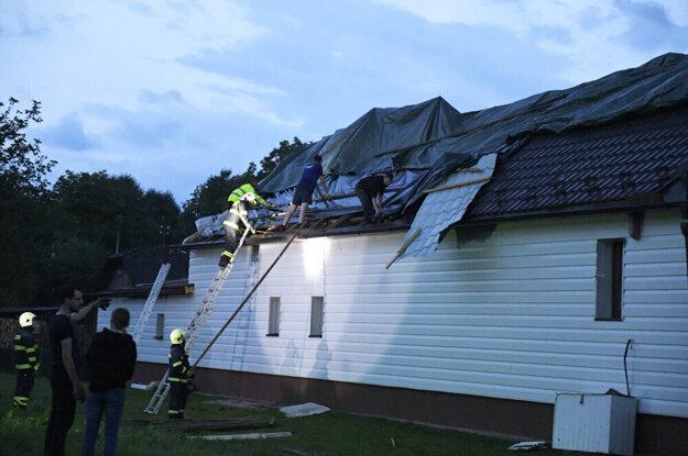 Poškodená strecha domu po tornáde v Petkovciach.