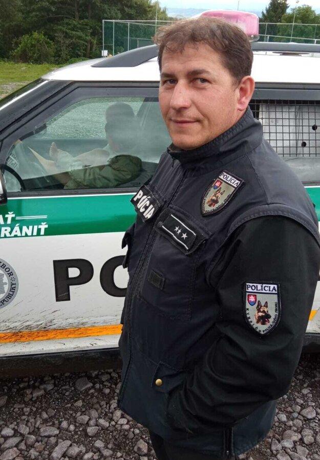 Policajt, ktorý chlapca našiel, a dieťa už v bezpečí v policajnom aute.