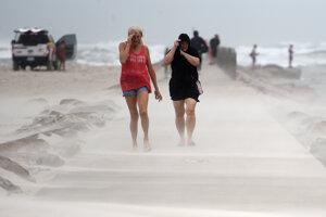 Ľudia v Texase si kryjú tvár pred silným vetrom z tropickej búrky Nicholas.