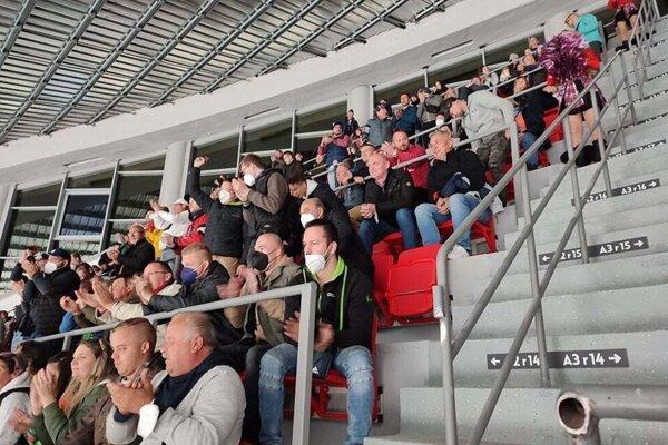 Prví fanúšikovia usadení na nových sedačkách na zimnom štadióne.
