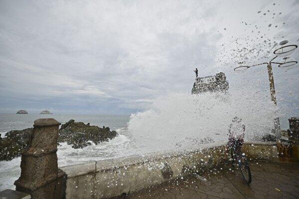 Cyklistu zasiahla nárazová vlna na pláži Pinitos pred príchodom tropickej búrky Pamela v mexickom Mazatlane.