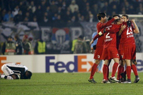 Je koniec. Futbalisti Augsburgu oslavujú postup, hráč domáceho Partizanu smúti nad premárnenou šancou.