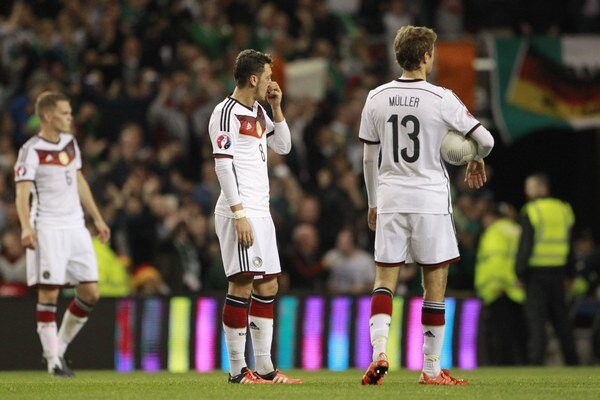 Futbalisti Nemecka smutne postávajú po tom, ako sa Írom podarilo skórovať do ich siete.