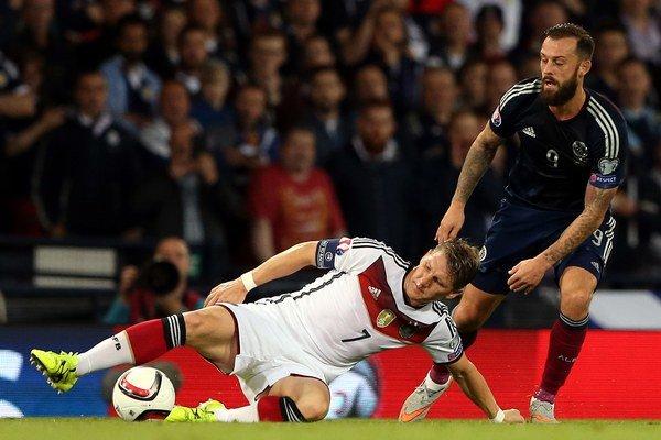 Kapitán Nemecka Bastian Schweinsteiger (vľavo) v súboji so Škótom Stevenom Fletcherom.