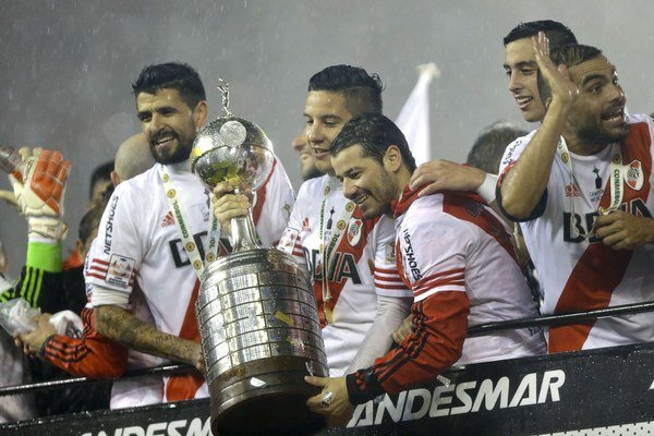 Futbalisti River Plate oslavujú víťazstvo v Pohári osloboditeľov s majstrovskou trofejou v rukách.