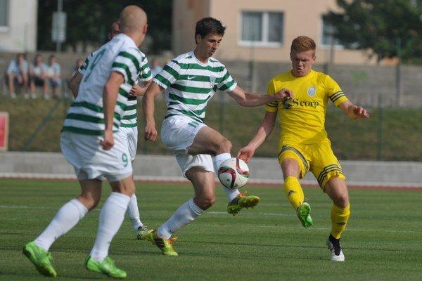 Michalovčan Jakub Grič (v žltom) bojuje o loptu s presilou domácich futbalistov.