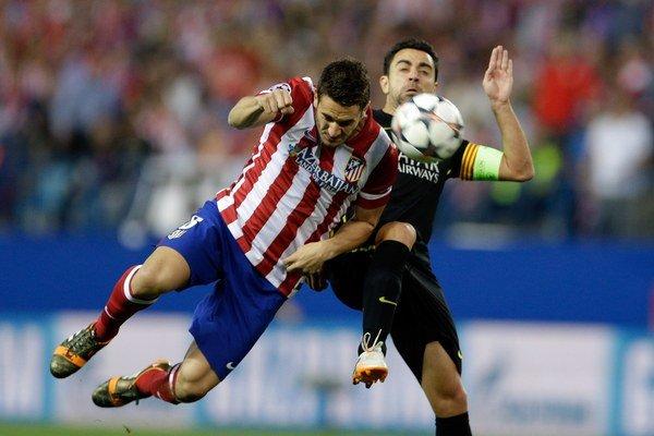 Koke (vľavo) rozhodol o postupe Atlética cez Barcelonu. O loptu bojuje so svojím idolom Xavim.
