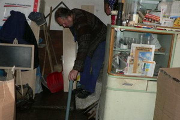 Starší pán ukazuje stav vody vo svojej pivnici.