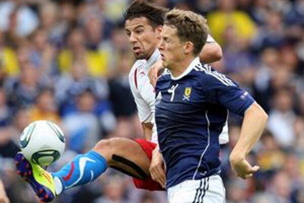 Český futbalista Milan Baroš a Škót Christophe Berra počas kvalifikačného zápasu o postup na EURO 2012 v škótskom Glasgowe.