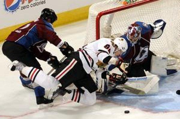 Obranca Colorado Avalanche Scott Hannan (č.22) a Slovák Tomáš Kopecký z Chicaga Blackhawks (č. 82) v súboji o puk. Chicago prehralo 3:4.