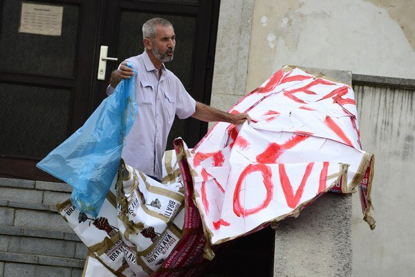 Starosta obce Vincent Leššo odstraňuje transparent proti fašizmu, ktorí pripravili aktivisti.