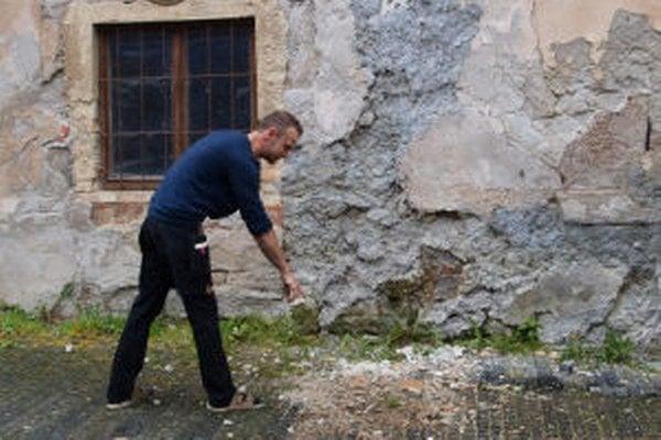 """""""Bola to poriadna šupa,"""" ukazuje na zvyšky popadanej omietky na chodníku Michal Mihál pracujúci v kaviarni oproti chátrajúcej budove."""