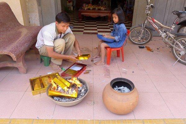 V uliciach Battambangu pália Číňania papierové symboly bohatstva.
