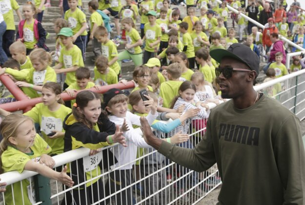 Jamajský šprintér Usain Bolt sa zdraví s deťmi počas detského atletického mítingu Čokoládová tretra v Prahe.