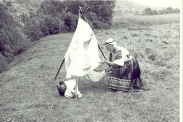 Žena z Podkoníc s dieťaťom v poľnej kolíske. 1. polovica 20. storočia.