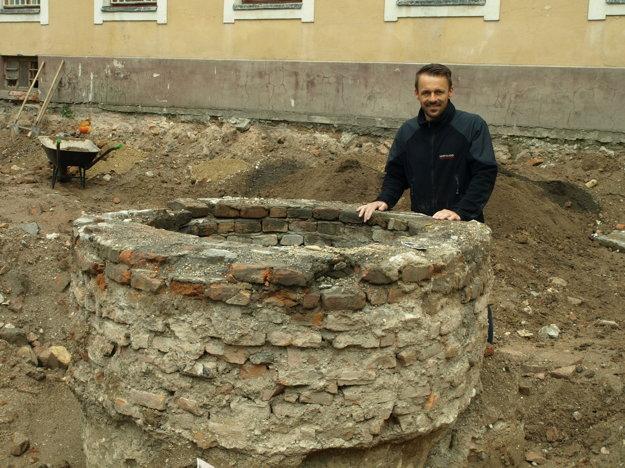 Archeológ Erik Hrnčiarik pri vzácnej barokovej studni.