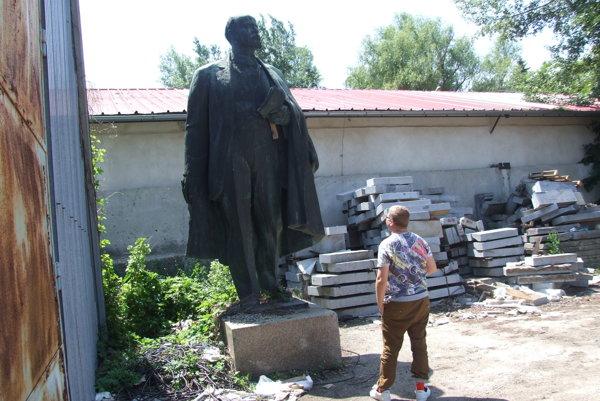 Lenin stojí za plechovým skladom.
