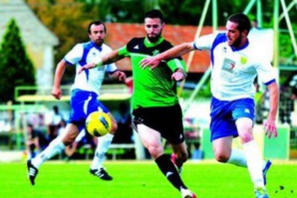 Útočník FKM Košút (v zelenom), bránený hráčmi Levíc.