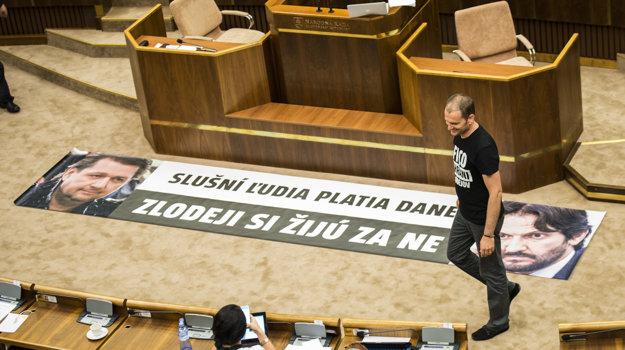 Igor Matovič rozkladá transparent s nápisom Slušní ľudia platia dane, zlodeji si žijú za ne.