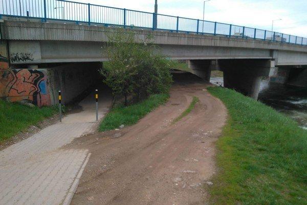 Vyjazdená cesta pod mostom. Motoristi si prejazdom týmto miestom ušetria cestu.