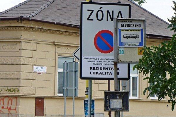 Skrývačky. Stĺpik zastávky kryje zónovú značku, tá zas značku Hlavná.