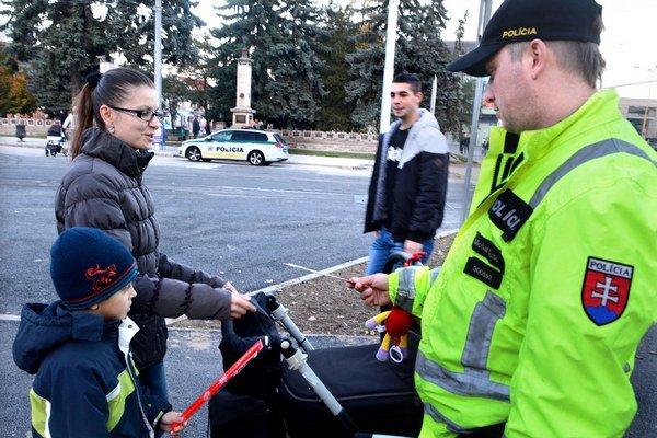 Reflexné pásky. Policajti ich rozdávajú, ľudia na ne kašlú.