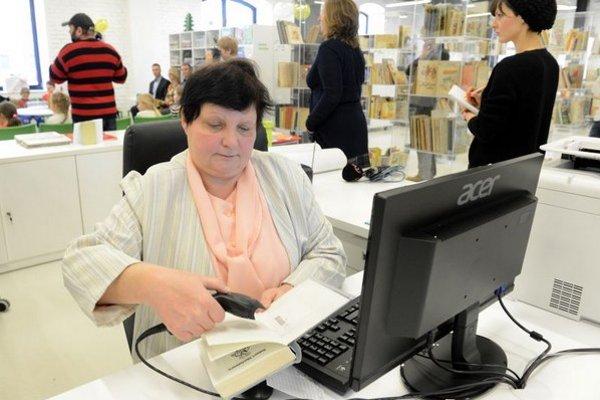 Na snímke pracovníčka knižnice skenuje kód vrátenej knihy.
