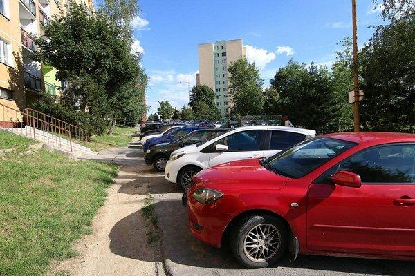 Autá stoja tak, že ľudia si vedľa chodníka museli vyšliapať cestičku, aby tadiaľ prešli.