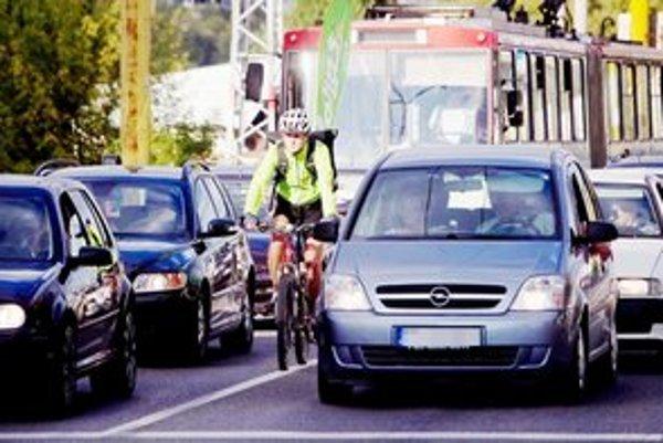 Kuriér v bežnej premávke. Jazdiť medzi autami je nebezpečné.