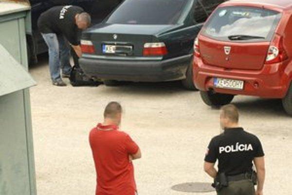 Podozrivý. Muž v strede sa mal zúčastniť únosu, potom sa prizeral, ako polícia prehľadáva auto.