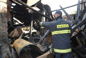 """Zhorenisko. """"Tam je treba ešte dohasiť tlejúce zvyšky,"""" ukazuje hasič kolegom."""