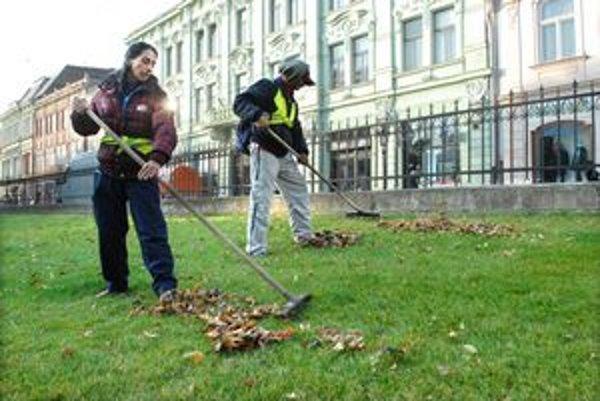 Jesenné práce. Z centra mesta opadané lístie hrabú a odvážajú do kompostárne.