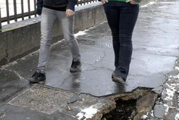 Chodník pri škole. Až jeho prelomenie ukázalo obrovskú dutinu pod asfaltom, bolo len otázkou času, kedy by sa prepadol úplne.