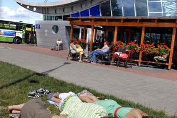 Nekonečné čakanie. Cestujúci si ho krátili aj spánkom na tráve pred letiskom.