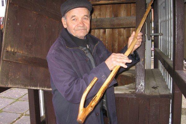 Dôchodca Jozef Guman ukazuje, na aký nástroj sa vešajú nádoby na naberanie vody z miestneho prameňa. Drevenú tyč nazývajú kvaka.