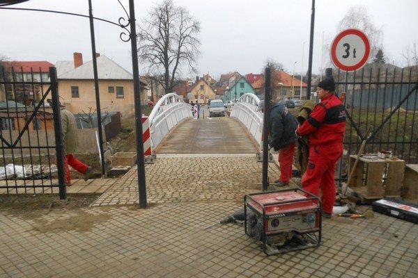 Osadzujú bránu. Stavbári dávajú plot do pôvodného stavu.