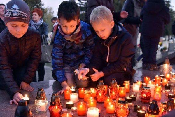 Na snímke pokladajú sviečky na mestskom cintoríne v Trebišove podvečer 1. novembra 2015.