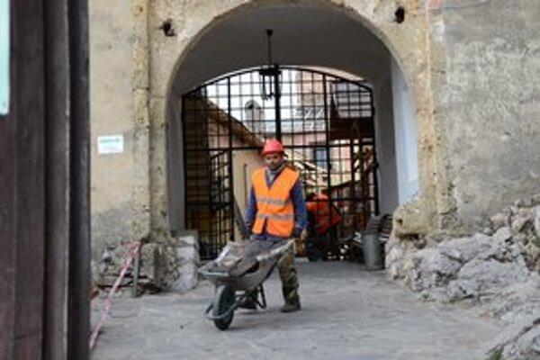 Dobrovoľníci upratujú hrad od zhorených materiálov.