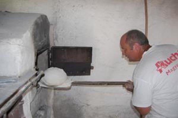 Pri peci. Je tam neznesiteľná horúčava, no tradičný pekár si už zvykol.